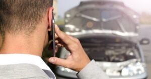 telefonáló férfi egy lerobbant kocsival szemben
